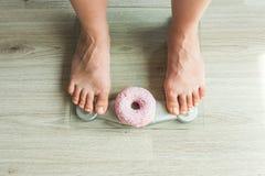 概念饮食 妇女在秤的` s脚特写镜头用多福饼 甜点、不健康的速食和肥胖病的概念 免版税图库摄影
