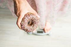 概念饮食 妇女在秤的` s脚特写镜头用多福饼 甜点、不健康的速食和肥胖病的概念 免版税库存照片