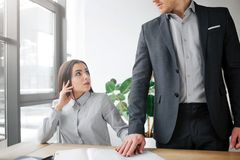 概念骚扰 害怕的年轻女人坐在桌和神色上在她的上司 她被惊吓 人握他的手在她顶部 库存图片