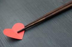 概念,筷子采取象一些食物的心脏 图库摄影