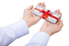 概念,金钱作为礼物 人` s用在衬衣的两只手采取或给堆100美金栓与与弓的红色丝带 库存照片
