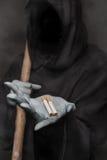 概念:抽烟的杀害 拿着香烟的死亡 免版税图库摄影