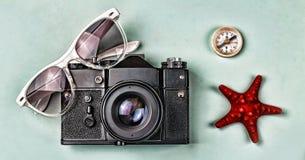 概念:旅行,假期,活跃休闲,海远航 古老照相机、太阳镜、老指南针和海星在一蓝色backgro 图库摄影