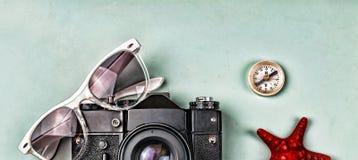 概念:旅行,假期,活跃休闲,海远航 古老照相机、太阳镜、老指南针和海星在一蓝色backgro 免版税库存照片