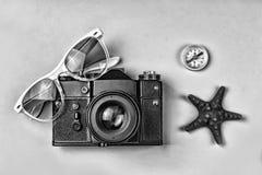 概念:旅行,假期,活跃休闲,海远航 古老照相机、太阳镜、老指南针和海星在一蓝色backgro 库存图片