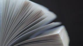 概念读书,书,翻转书 在黑暗的背景的书页 股票录像
