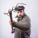 概念-恼怒的农夫 古板的衣裳的有胡子的人有在手中干草叉的,危险 免版税库存照片