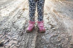概念-是愉快的童年 沼泽的,儿童` s乐趣,肮脏的鞋子,生活在村庄,阳光,背后照明孩子 库存图片