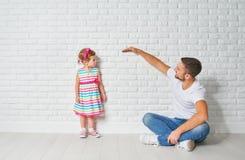 概念 爸爸测量她的儿童女儿成长在墙壁 免版税图库摄影