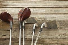 概略的木表面上的老高尔夫俱乐部 免版税库存照片