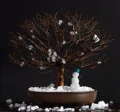 榆木与雪人的盆景树 免版税库存照片