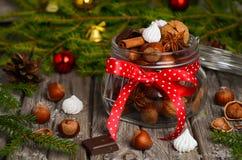 榛子和核桃与甜点和香料在一个玻璃瓶子 免版税库存照片