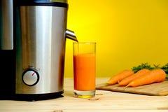 榨汁器和红萝卜汁在玻璃 库存照片