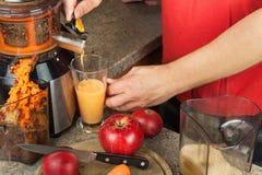 榨汁器和苹果汁 准备健康新鲜的汁液 家庭juicing的苹果在厨房里 处理秋季果子 库存照片