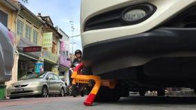 槟榔岛,马来西亚- 1月20日:在汽车的车轮固定夹 在旅游街道上的不正确停车处在乔治市 从地面的看法 影视素材