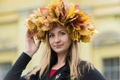 槭树叶子花圈的金发碧眼的女人  免版税库存图片