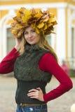 槭树叶子花圈的金发碧眼的女人  库存照片