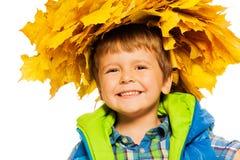 槭树花圈的小愉快的男孩在白色 库存图片