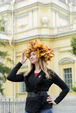 槭树花圈的白肤金发的女孩离开 免版税库存图片