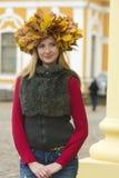 槭树花圈的白肤金发的女孩离开 库存照片