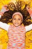 槭树黄色秋叶的愉快的非洲女孩 免版税库存照片