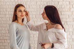 模型和化妆师做一个新的形式自然眼眉 免版税库存图片