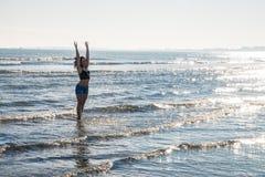 模型在海边在冬天 脚在水中与许多反射 免版税图库摄影