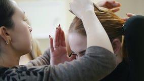 模型在演播室 美发师帮助模型紧固马尾辫 股票录像