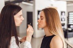 模型少妇cosmetologistt weezing的眼眉在秀丽交谊厅 免版税库存照片