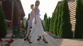 模型排成纵列前进户外,礼服的女孩在庭院里走并且看照相机 股票录像