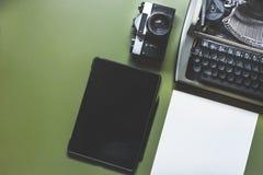 模式打字机、数字式片剂和影片照相机在选材台上,顶视图 免版税图库摄影