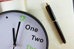 模式时钟和笔投入了空的笔记本纸 免版税库存照片
