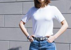 模板和大模型摆在对灰色街道墙壁的空白白色T恤和牛仔布,印刷品商店的 免版税库存照片