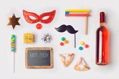 模板的犹太假日普珥节嘲笑与狂欢节面具, hamantaschen曲奇饼和酒瓶 在视图之上 库存照片