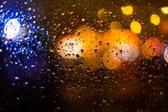 模糊的城市和通过湿车窗看的红绿灯 免版税库存图片