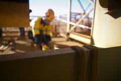 模糊装配工人图片连接的黄色三口气尼龙纤维起重吊具入在射线结构附近 免版税图库摄影