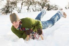 横向人骑马爬犁多雪的年轻人 图库摄影