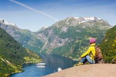 横向山美丽如画的挪威 享受看法的女孩在Geiranger海湾,挪威附近 免版税库存图片