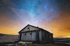 横向晚上人街道走的冬天 被放弃的木房子在夜满天星斗的天空的背景中在明亮的颜色和日落的 免版税库存图片