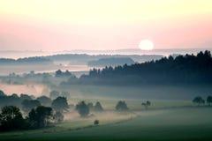 横向有薄雾的超出日落