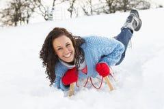 横向骑马爬犁多雪的妇女年轻人 免版税库存照片