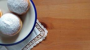 横幅-说谎在土气木桌上的陶瓷板材的油炸圈饼顶上的看法  批次复制空间 库存照片