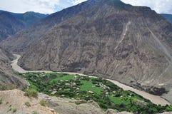 横断山脉西藏左贡县,从村庄的了不起的动量通过Nu河 库存图片