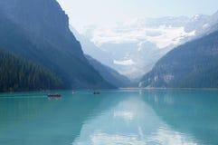横断路易丝湖,有积雪覆盖的山的加拿大的天蓝色的水划独木舟的人作为背景 免版税库存图片