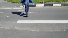 横渡一条行人交叉路的一个成人人 因为他有大脑麻痹,他在一条腿跛行 股票视频