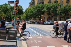 横渡一条行人交叉路的骑自行车者在一个夏日 免版税库存图片