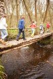 横渡在木桥的小组孩子小河 免版税库存照片