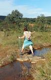 横渡在石头的年长妇女一条小小河,远足在山脉Norte de塞维利亚自然公园,西班牙 库存照片