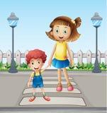 横渡步行者的小孩儿和女孩 免版税库存照片