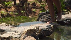 横渡河水的女性腿流动在石头在山 跑和跳过岩石河的赤足妇女 影视素材